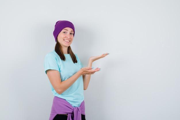 Jonge vrouw weergegeven in blauw t-shirt, paarse muts en vrolijk kijken. vooraanzicht.