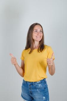 Jonge vrouw wegkijken met duimen omhoog in geel t-shirt, korte broek en op zoek vrolijk