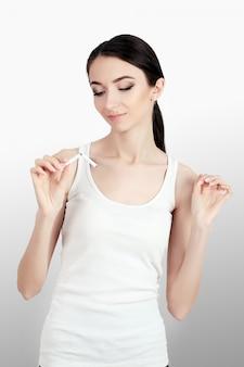 Jonge vrouw weigert te roken en breekt sigaretten.