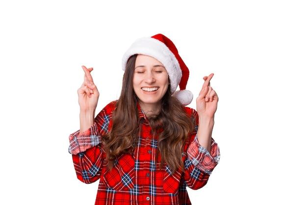 Jonge vrouw wenst iets voor kerstmis met gesloten ogen.