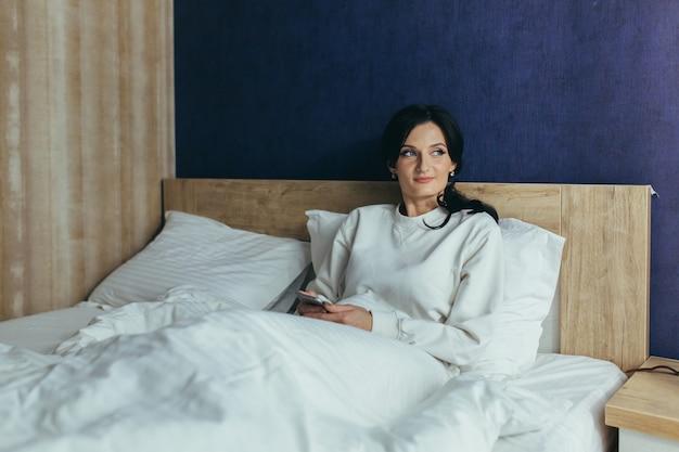 Jonge vrouw werd 's ochtends wakker in de slaapkamer