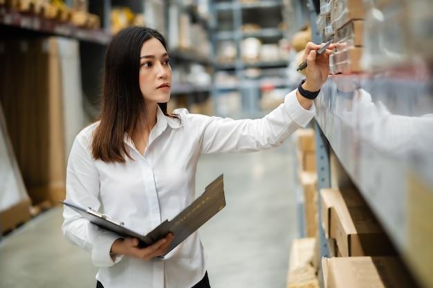 Jonge vrouw werknemer klembord houden en controleren van de inventaris in het magazijn