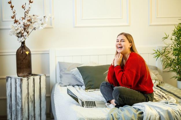Jonge vrouw werkt op een computer, zittend op een bed, op afstand werkend. een meisje met lang haar in een rode trui en spijkerbroek werkt thuis.