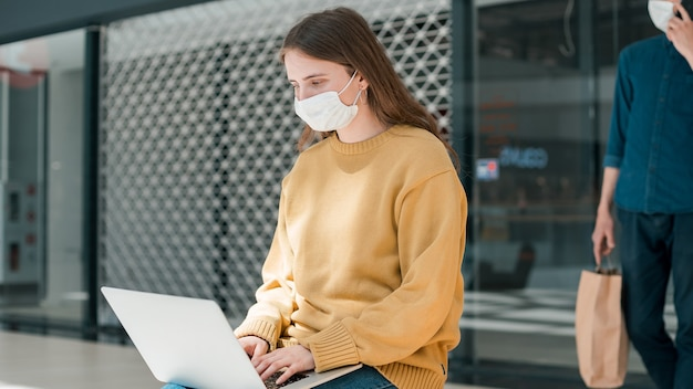 Jonge vrouw werkt op een laptop terwijl ze buiten een stadsgebouw zit