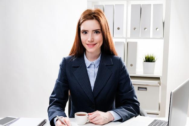 Jonge vrouw werkt op kantoor op de computer