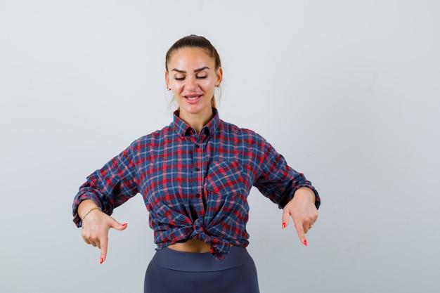 Jonge vrouw wijst naar beneden in geruit overhemd, broek en ziet er gelukkig uit. vooraanzicht.