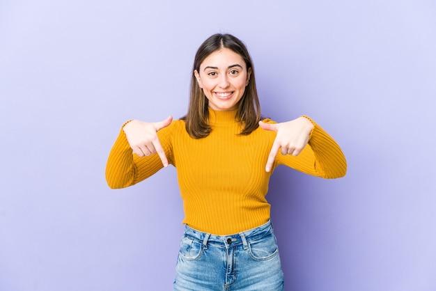 Jonge vrouw wijst naar beneden met vingers, positief gevoel