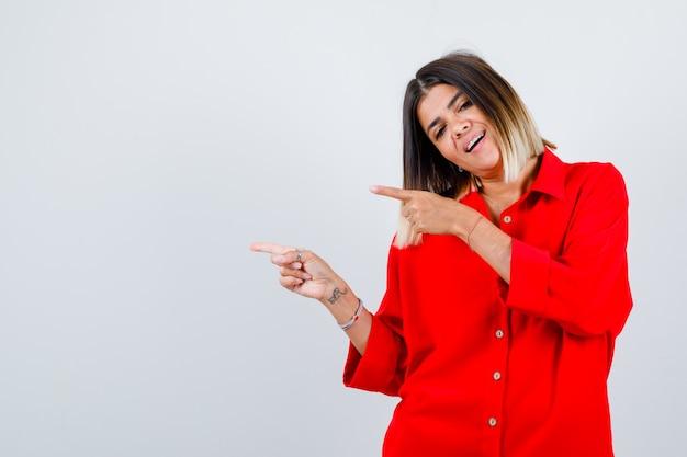 Jonge vrouw wijst naar de linkerkant in een rood oversized shirt en ziet er gelukkig uit. vooraanzicht.