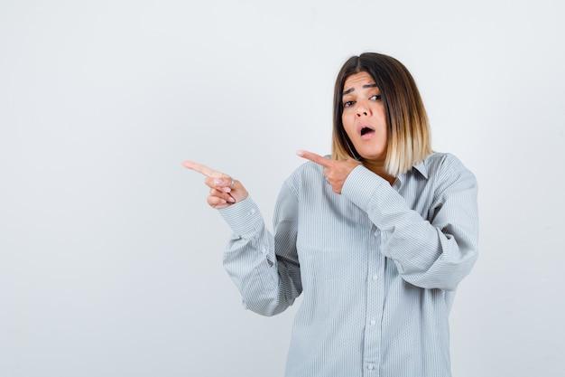 Jonge vrouw wijst naar de linkerkant in oversized shirt en kijkt verbijsterd. vooraanzicht.