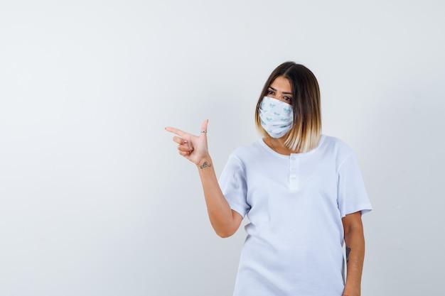 Jonge vrouw wijst naar de linkerkant in t-shirt, masker en kijkt zelfverzekerd, vooraanzicht.