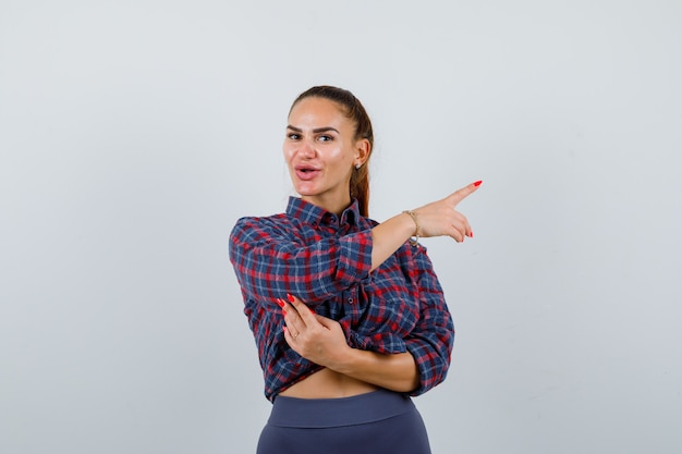 Jonge vrouw wijst naar de rechterkant in geruit hemd, broek en ziet er zelfverzekerd uit. vooraanzicht.