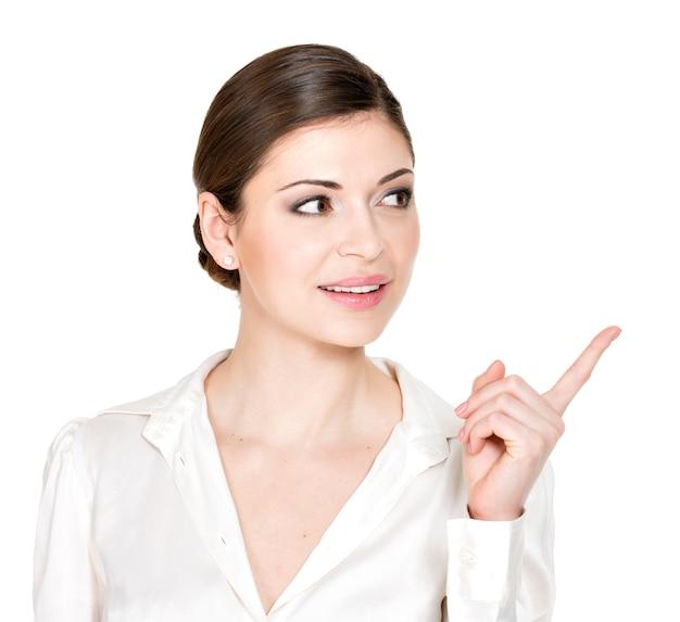 Jonge vrouw wijst naar de zijkant in wit overhemd -.