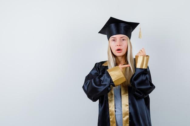 Jonge vrouw wijst naar haar mouw in afgestudeerd uniform en kijkt verrast