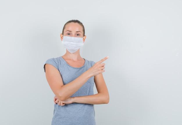 Jonge vrouw wijst naar kant in grijs t-shirt, masker, vooraanzicht.