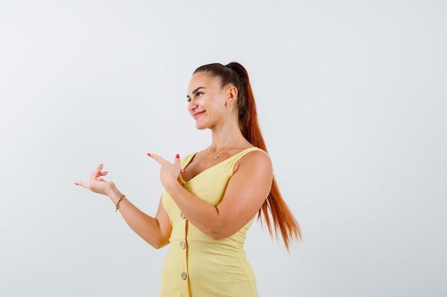Jonge vrouw wijst naar links in gele jurk en ziet er vrolijk uit