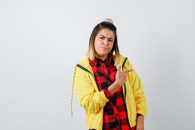 Jonge vrouw wijst naar rechts in geruit overhemd, jasje en peinzend kijkend. vooraanzicht.