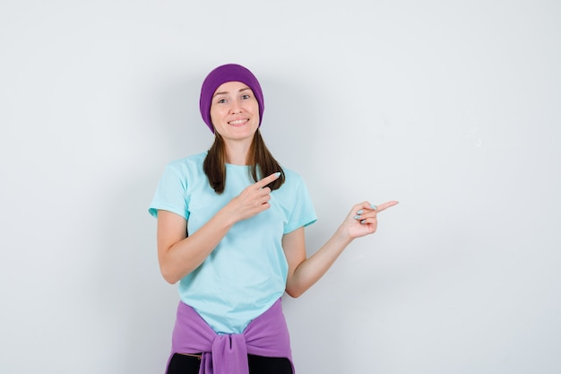 Jonge vrouw wijst naar rechts met wijsvingers in blauw t-shirt, paarse muts en ziet er vrolijk uit, vooraanzicht.