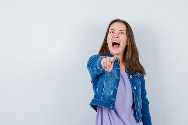 Jonge vrouw wijst naar voren in t-shirt, jas en ziet er gek uit. vooraanzicht.