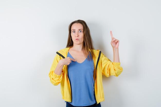 Jonge vrouw wijst naar zichzelf en omhoog in t-shirt, jas en kijkt verrast, vooraanzicht.