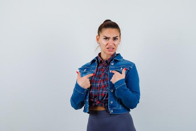 Jonge vrouw wijst naar zichzelf in geruit hemd, jas, broek en kijkt hulpeloos, vooraanzicht.