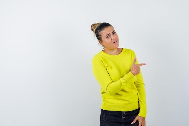Jonge vrouw wijst opzij in trui, spijkerrok en ziet er zelfverzekerd uit