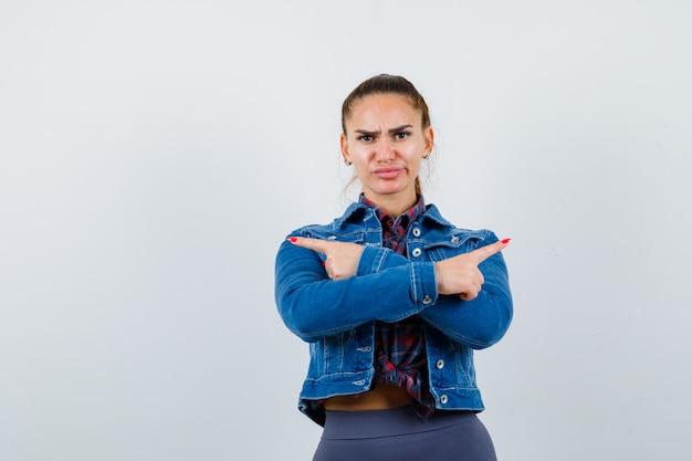 Jonge vrouw wijst opzij met gekruiste armen in geruit hemd, spijkerjasje en kijkt ontevreden, vooraanzicht.