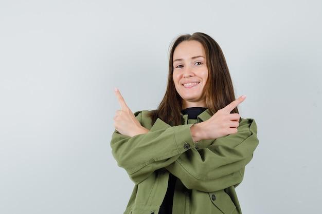 Jonge vrouw wijst opzij met gekruiste armen in groene jas en kijkt verward. vooraanzicht.