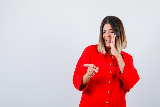 Jonge vrouw wijst opzij terwijl ze de hand aan de zijkant van de mond houdt in een rood oversized shirt en er gelukkig uitziet. vooraanzicht.