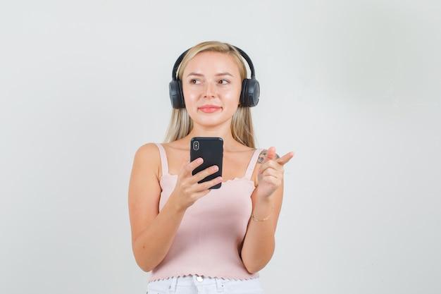 Jonge vrouw wijst weg en houdt smartphone in singlet