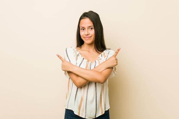 Jonge vrouw wijst zijwaarts, probeert te kiezen tussen twee opties.