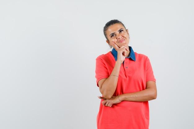 Jonge vrouw wijsvinger op wang zetten, denken over iets in rood t-shirt en peinzend, vooraanzicht kijken.