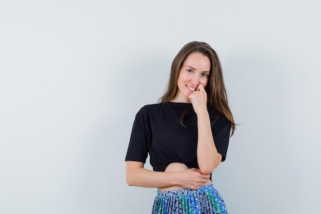 Jonge vrouw wijsvinger zetten in de buurt van mond terwijl poseren op camera in zwart t-shirt en blauwe rok en gelukkig kijken Gratis Foto