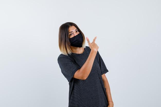 Jonge vrouw wijzend achter met wijsvinger in zwarte jurk, zwart masker en op zoek gelukkig, vooraanzicht.