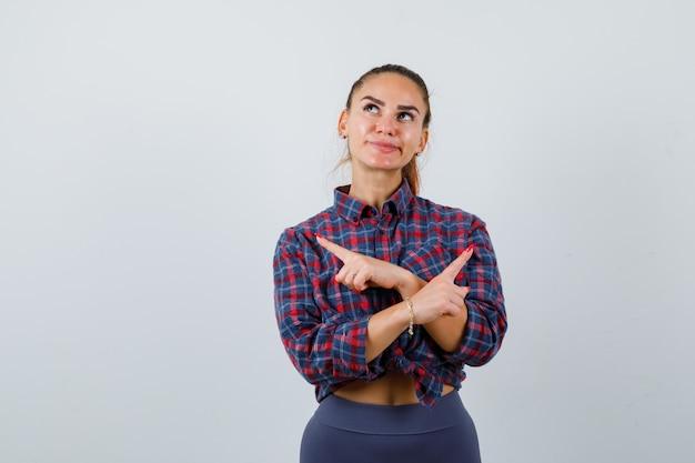 Jonge vrouw wijzend naar beide hoeken in geruit hemd, broek en aarzelend kijkend, vooraanzicht.