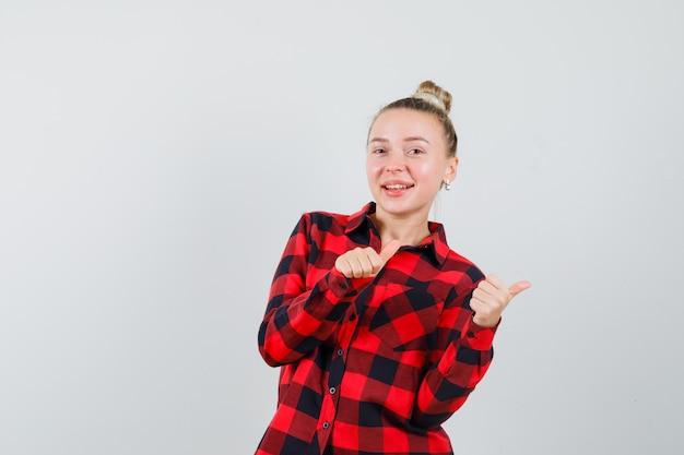 Jonge vrouw wijzend naar de kant met duimen omhoog in geruit overhemd en op zoek dartel