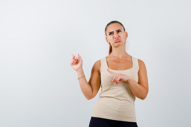 Jonge vrouw wijzend naar de linkerbovenhoek in beige tanktop en kijkt beledigd, vooraanzicht.