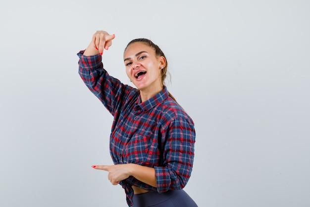 Jonge vrouw wijzend op camera en linkerkant in geruit hemd, broek en op zoek gelukkig, vooraanzicht.
