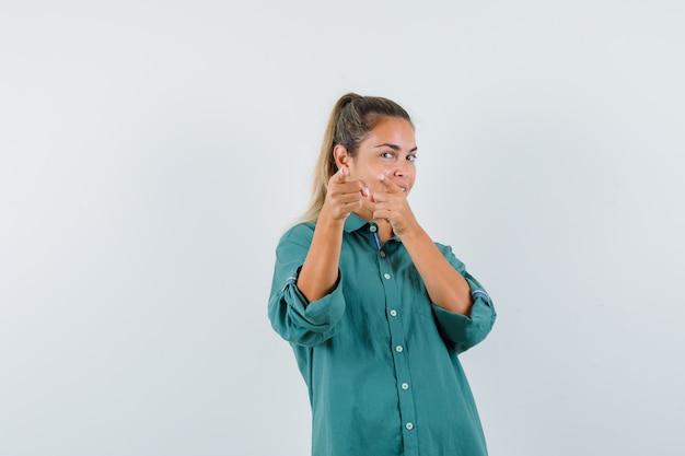 Jonge vrouw wijzend op camera in blauw shirt en gefocust op zoek