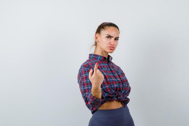 Jonge vrouw wijzend op camera in geruit hemd, broek en serieus, vooraanzicht.