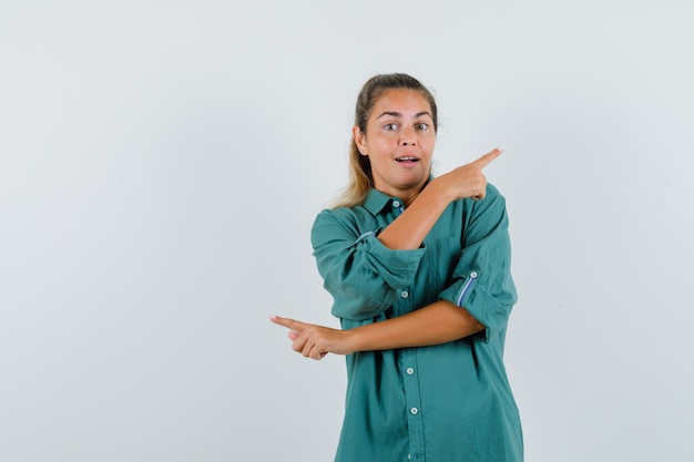 Jonge vrouw wijzend op de achterkant in blauw shirt en kijkt verbaasd