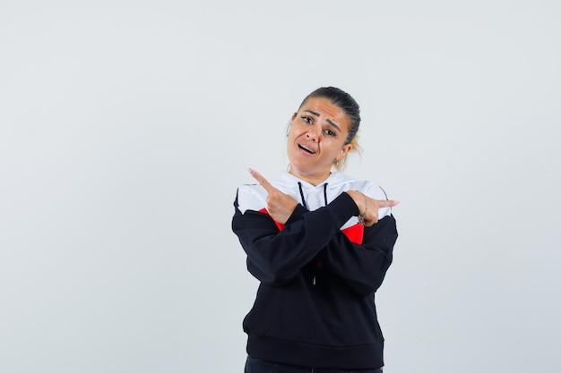 Jonge vrouw wijzend op de achterkant in kleurrijke sweater en kijkt verward, vooraanzicht.