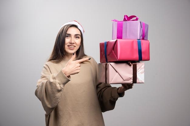 Jonge vrouw wijzend op drie dozen met kerstcadeautjes.
