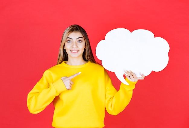 Jonge vrouw wijzend op een tekstballon op rood