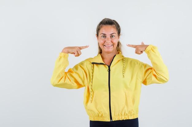 Jonge vrouw wijzend op haar glimlach in gele regenjas