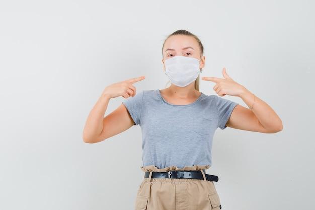 Jonge vrouw wijzend op haar medisch masker in t-shirt, broek, vooraanzicht.