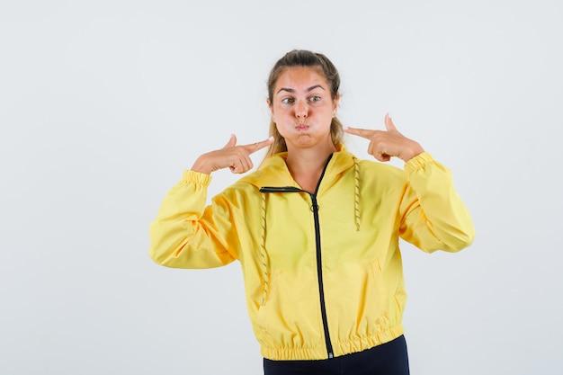 Jonge vrouw wijzend op haar opgeblazen wangen in gele regenjas en ziet er raar uit