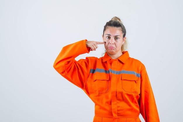 Jonge vrouw wijzend op haar tranen terwijl ze huilen in uniform van de werknemer en boos kijkt. vooraanzicht.