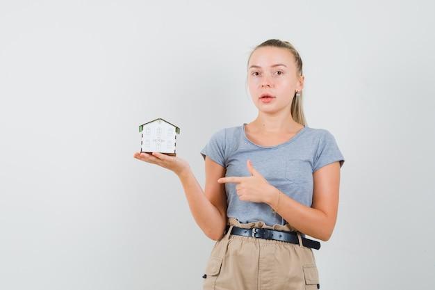 Jonge vrouw wijzend op huismodel in t-shirt, broek en op zoek verstandig, vooraanzicht.