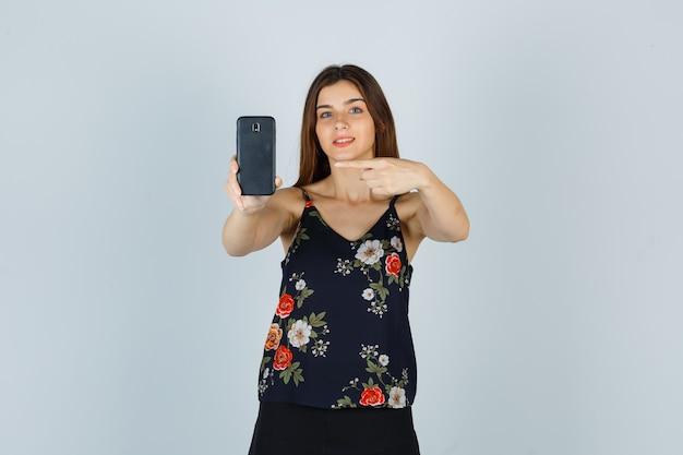 Jonge vrouw wijzend op smartphone in blouse, rok en vrolijk, vooraanzicht.