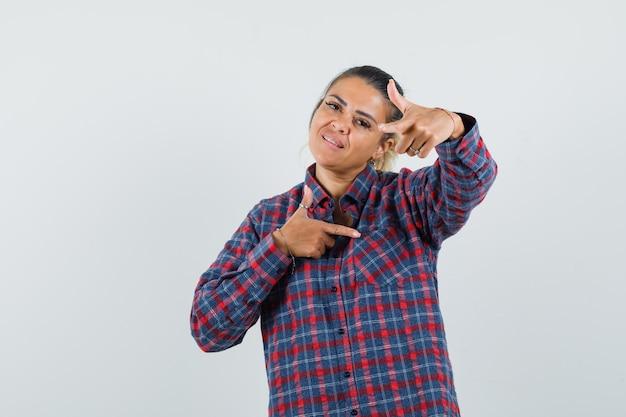 Jonge vrouw wijzend op verschillende richtingen met beide wijsvingers in geruit overhemd en op zoek naar optimistisch, vooraanzicht.